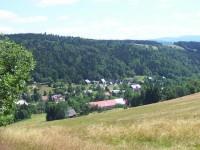 Dolní část obce v létě: Napravo se modrají západní Krkonoše