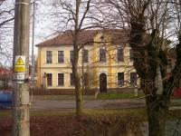 Obecní dům s pomníkem za potokem