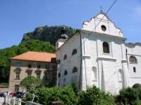 klášter a kostel Narození sv. Jana Křtitele v pozadí skála s křížem