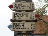 Nedvědice - rozcestník u kostela I.: První část rozcestníku u nedvědického kostela. Červená a jedna cedule modré značky.