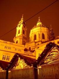 Noční pohled z Malostranského náměstí: Na Malostranském náměstí stával gotický farní kostel sv. Mikuláše vystavěný po r. 1283. Ten byl po r. 1620 v rámci rekatolizace zásluhou Albrechta z Valdštejna předán jezuitům a fara byla přeložena k sousednímu