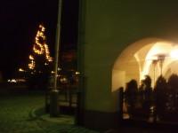 Podloubí budovy muzea s pizzerií a rozsvícený vánoční strom
